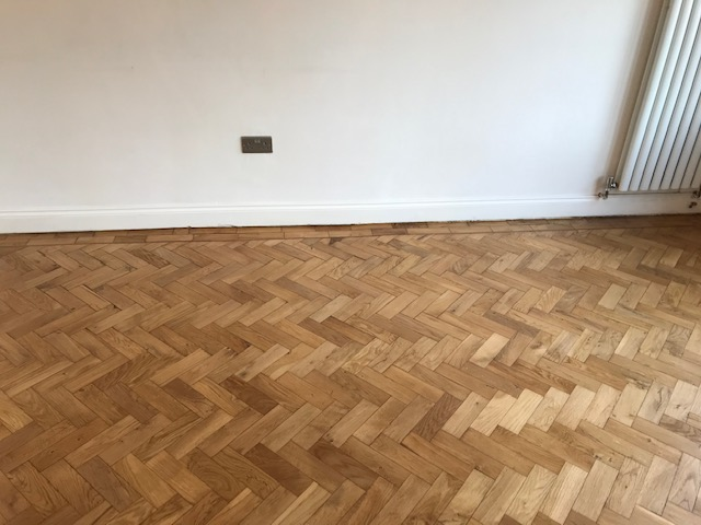 example of Gap filling and reclaiming of herringbone flooring in a living room, Mayfair